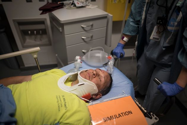 Anthony Aquan-Assee, a volunteer actor, is rolled towards the hallway during a mass casualty simulation...