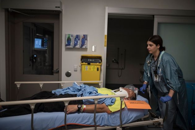 Diana Kanlic, a respiratory therapist, transports Anthony Aquan-Assee, a volunteer actor, during a mass...