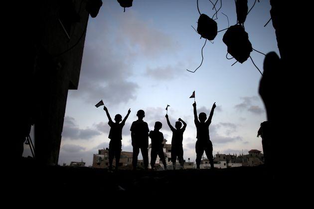 Unos niños juegan en un momento de tregua entre las ruinas de unas casas en el barrio de Shejaiya,...