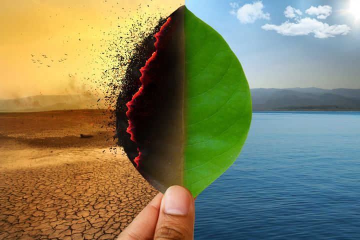 Climate change and Global warming concept. Burning leaf at land of cracked earth metaphor drought and Green leaf with river and beautiful clear sky metaphor Abundance of Nature.
