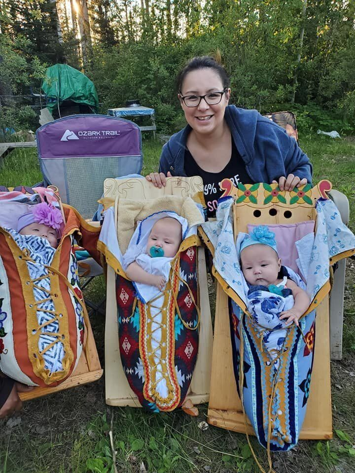 Michelle Kakegamic has been carrying her three daughters Hiliary Rose, Heather Grace, and Haddison Joy in tikinagans since they were discharged from the hospital.