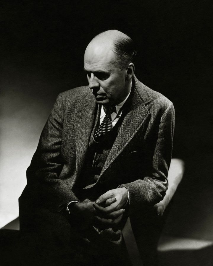 Artist, Edward Hopper, wearing a three-piece tweed suit, and polka dot tie, sitting in an arm chair in partial shadow, and looking down with a somber expression. (Photo by Lusha Nelson/Condé Nast via Getty Images)
