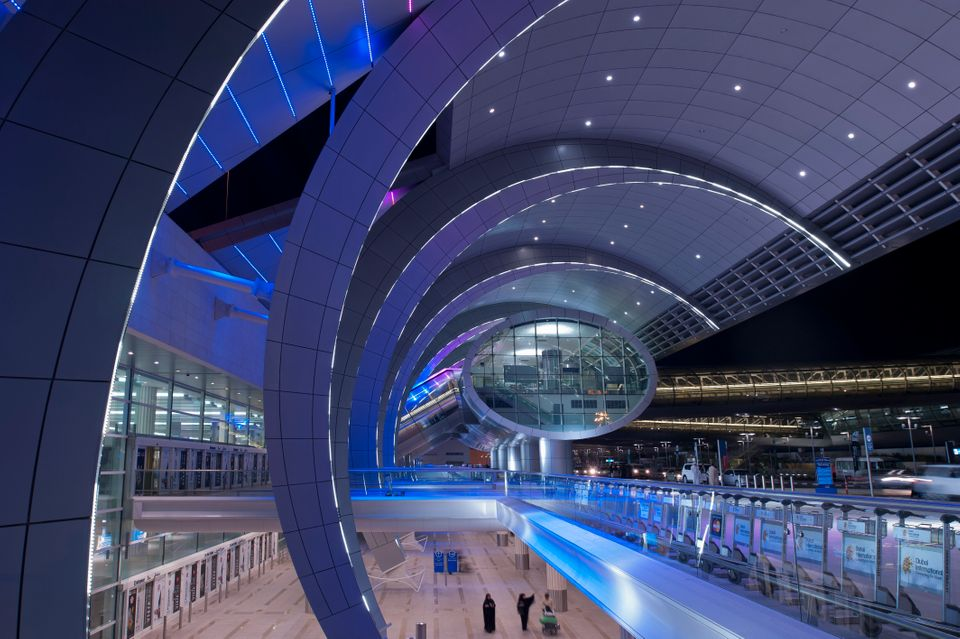 Dubai, UAE - November 18, 2011: People moving around the futuristic looking Dubai Airport, home to the...