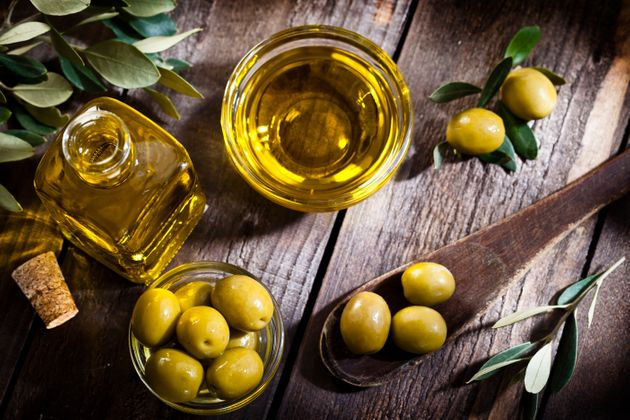 Top view of an olive oil bottle and a little glass bowl filled with green olives on rustic wood table....