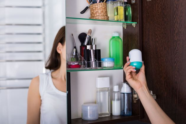 Morning routine. Young woman using cosmetics at her