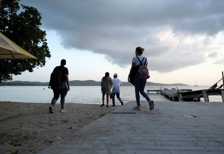 A group of people walk on the beach in the tourist zone of Boqueron as Tropical Storm Dorian approaches in Cabo Rojo, Puerto