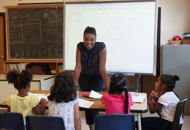 A teacher is seen in a classroom in a stock