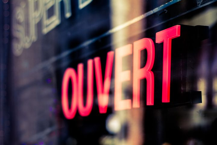 Open sign in French language on glass storefront