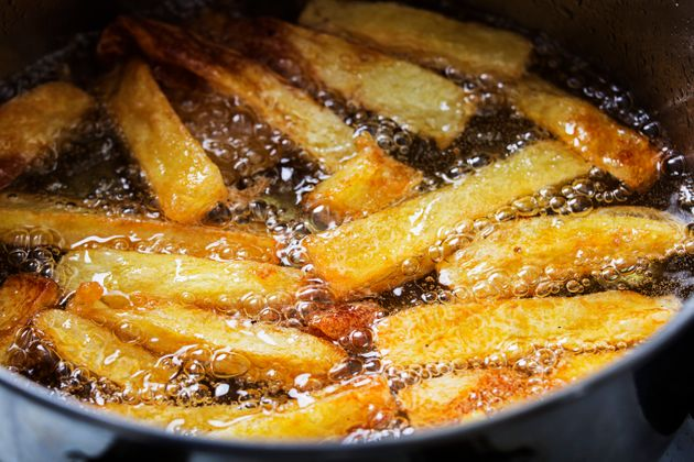French fries fry in hot bubbling oil in a frying
