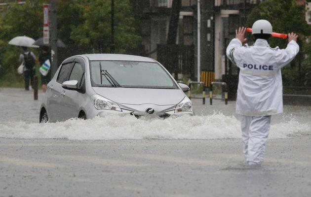 大雨で冠水した道路を進む車=8月28日午前、佐賀市
