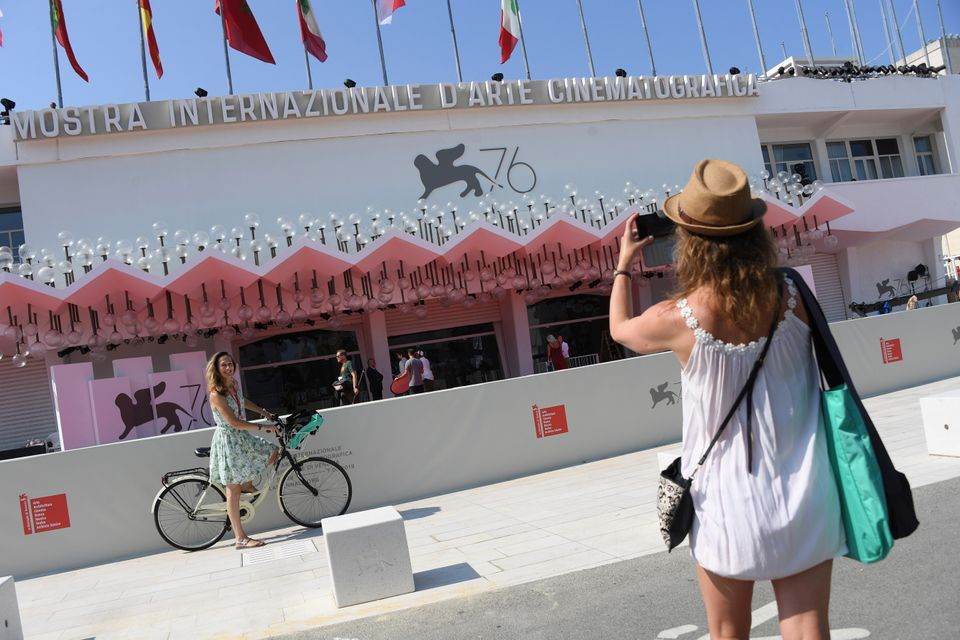 A festival goer has her picture taken in front of the Sala Grande cinema at the 76th edition of the Venice...