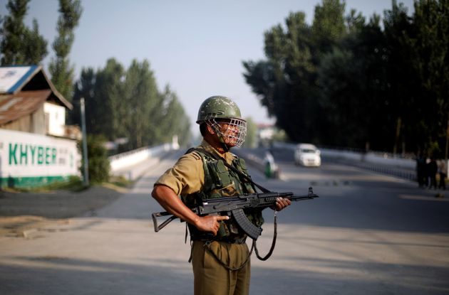 A security personnel stands guard on a deserted road during restrictions in Srinagar, August 23,
