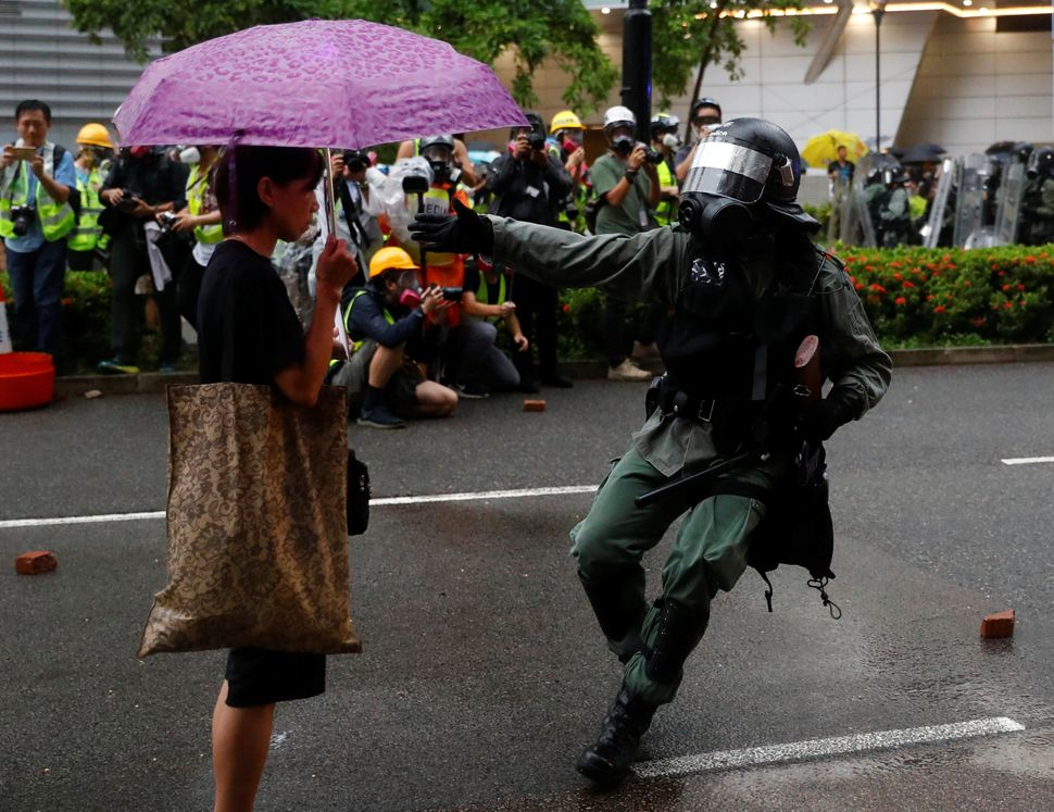 Riot police officer approaches a demonstrator during a protest in Tsuen Wan, in Hong Kong, August 25, 2019.