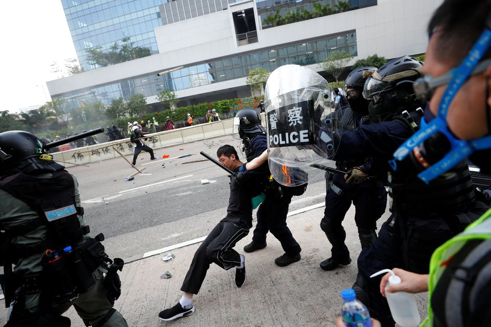 Riot police detain a demonstrator as they clash during a protest in Hong Kong, August 24,