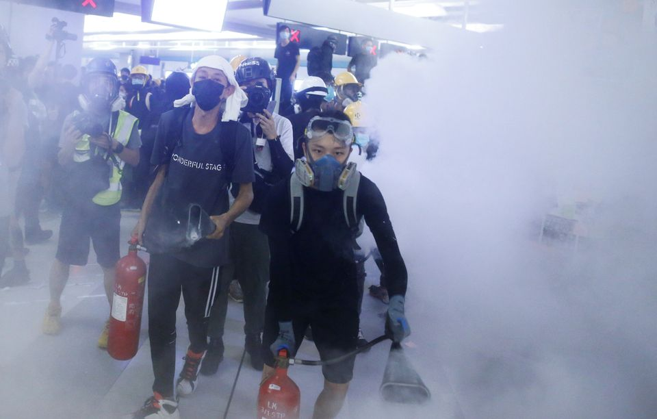 Protesters fire nitrogen extinguishers during a stand off at Yuen Long MTR station, the scene of an attack...