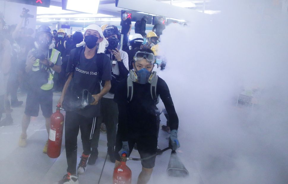 Protesters fire nitrogen extinguishers during a stand off at Yuen Long MTR station, the scene of an attack by suspected triad