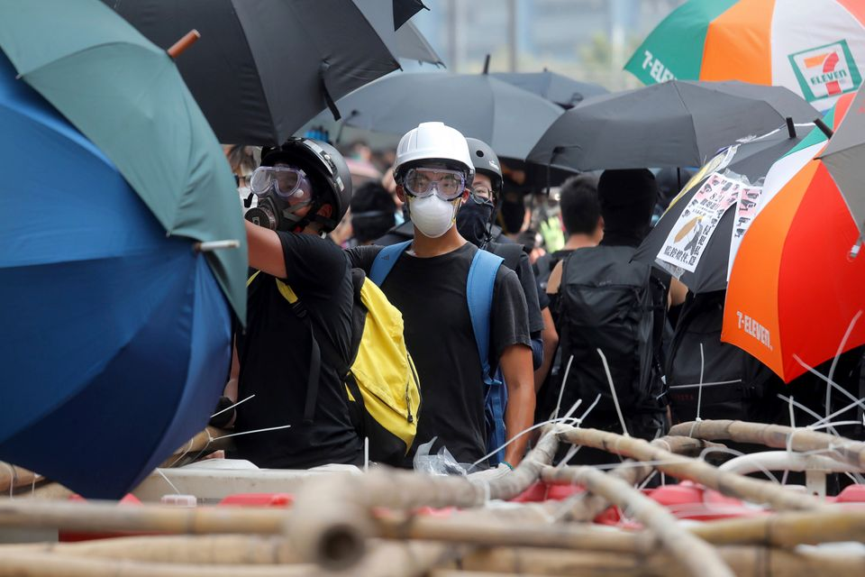 A demonstrator stands at a barricade made of bamboo poles during a protest in Hong Kong, Saturday, Aug....