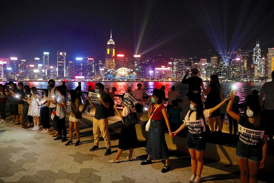 Demonstrators link hands as they gather at the Tsim Sha Tsui waterfront in Hong Kong, Friday, Aug. 23,