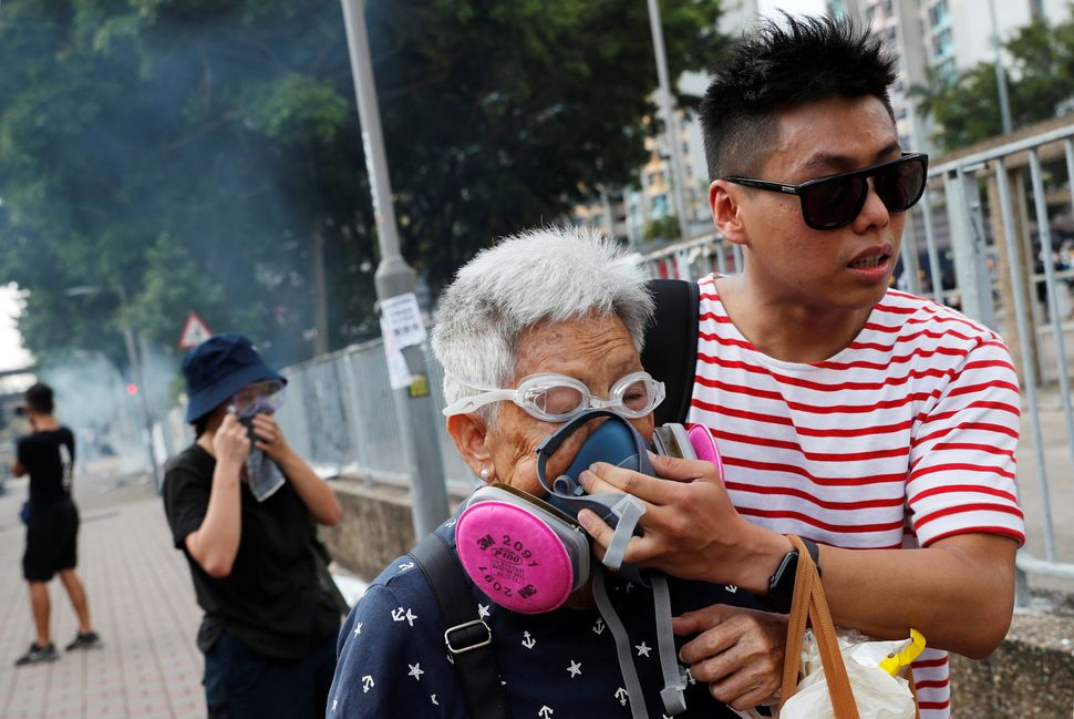 A woman is helped by a demonstrator after police fired tear gas during a demonstration in support of the city-wide strike and