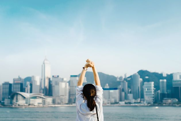 Rear view of woman traveller enjoying her time in Hong Kong, taking a deep breath with hands raised against...