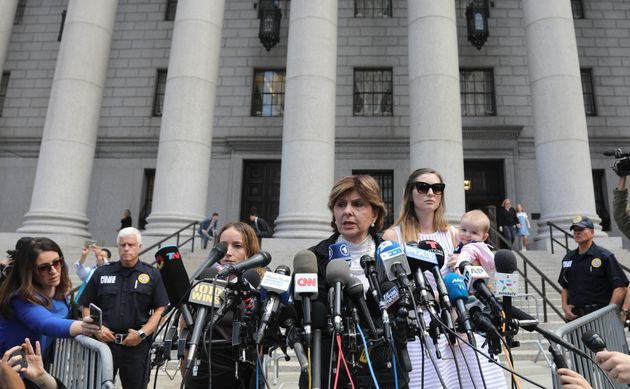 Attorney Gloria Allred, center, flanked by two of her clients, speak during a news conference after leaving...