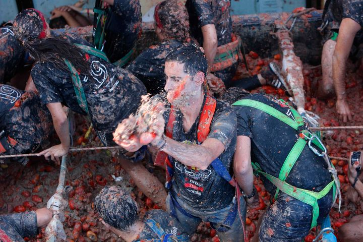 """Revellers throw tomatoes at each other during the annual """"Tomatina"""" tomato fight fiesta in the village of Bunol near Valencia"""