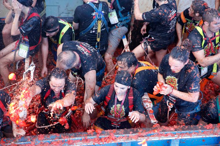 """Revellers throw tomatoes at each other, during the annual """"Tomatina"""" tomato fight fiesta in the village of Bunol near Valenci"""