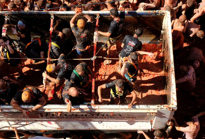 """Revellers on a truck throw tomatoes into the crowd during the annual """"La Tomatina"""" food fight festival in Bunol, near Valenci"""