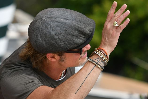 US actor Brad Pitt waves as he arrives by taxi boat on August 28, 2019 during the 76th Venice Film Festival...