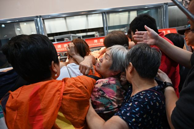 TOPSHOT - People try to get a roast chicken at the first Costco outlet in China, on the stores opening...
