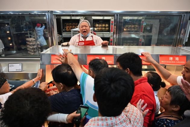 People try to get a roast chicken at the first Costco outlet in China, on the stores opening day in Shanghai...