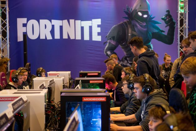 People play at computers with a Fortnite poster in the background during the Intel Extreme Masters Katowice...