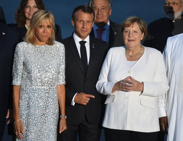 French President Emmanuel Macron, his wife Brigitte Macron and German Chancellor Angela Merkel pose for a family photo during the G7 summit in Biarritz, France, August 25, 2019. Andrew Parsons/Pool via Reuters