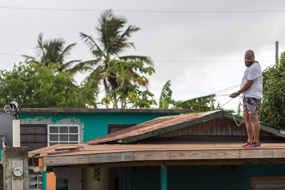 Lemuel Otero, 40, battening down the roof at his property in Maternillo, Fajardo, as Puerto Rico prepares to be hit by Tropic