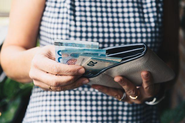 Una mujer saca billetes de 20 euros de su