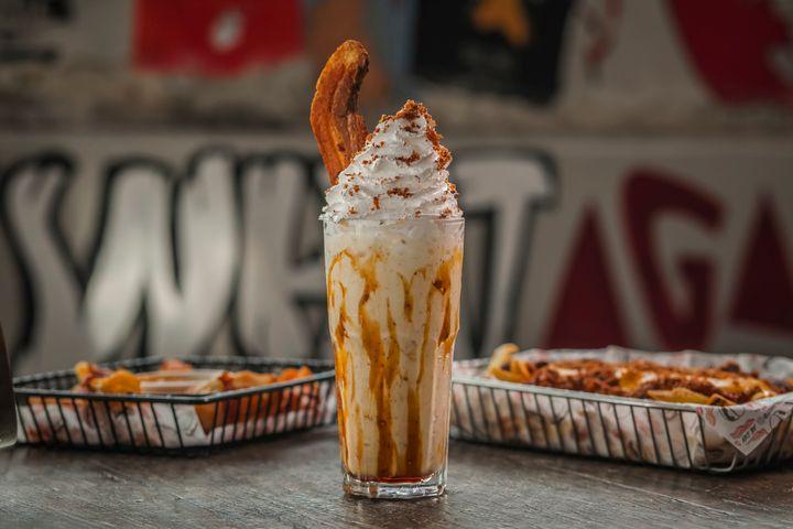 Porky Shake:milk shake com sorvete de creme, xarope de bordo, farofa de bacon crocante e chantilly, acompanhado de fatia de bacon de costela.