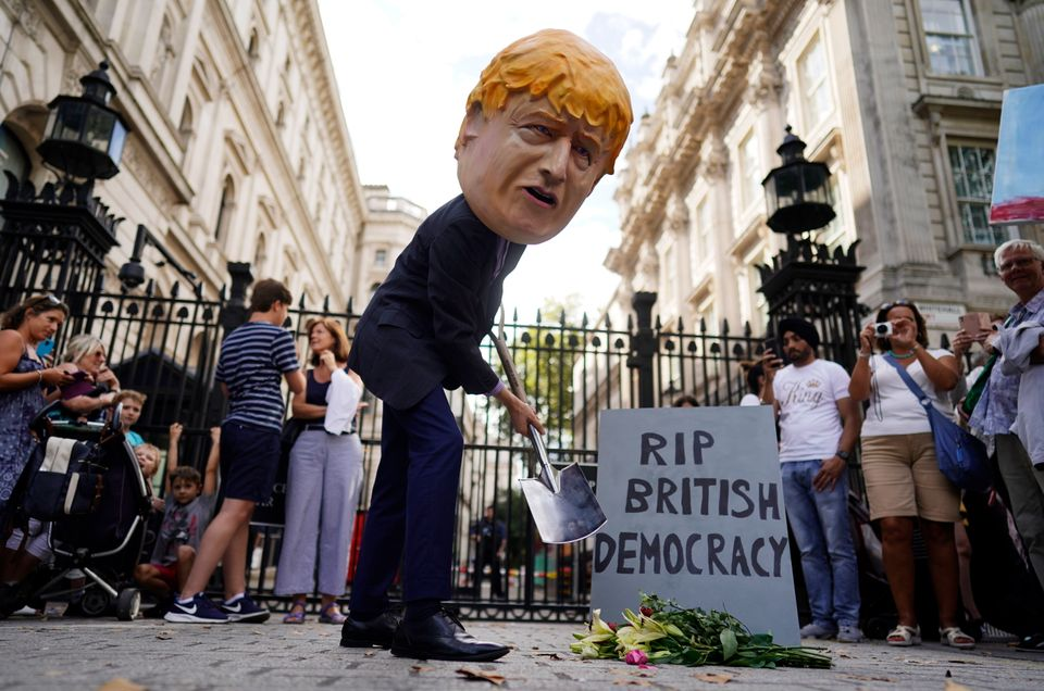 A protester depicting British Prime Minister Boris Johnson demonstrates with a spade outside Downing...