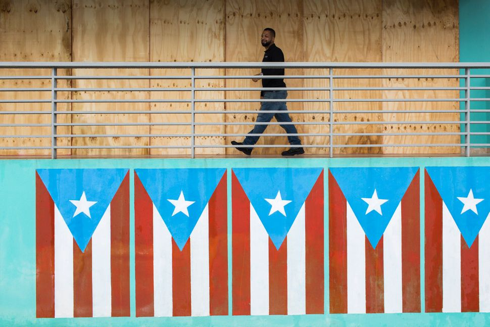A man finish boarding up restaurant at the Naguabo Malecon. Puerto Rico prepares to receive the hit of Tropical Storm Dorian