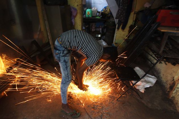 A worker cuts a metal pipe inside a workshop in Mumbai, India on 22 August 2019. (Photo by Himanshu Bhatt/NurPhoto...