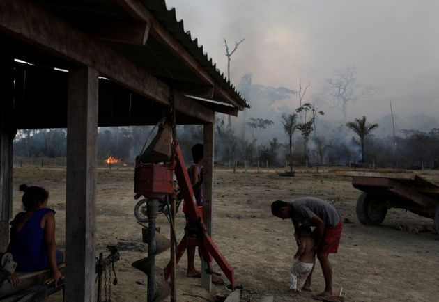 Residents are pictured while a fire burns a tract of Amazon jungle as it is cleared by loggers and farmers...