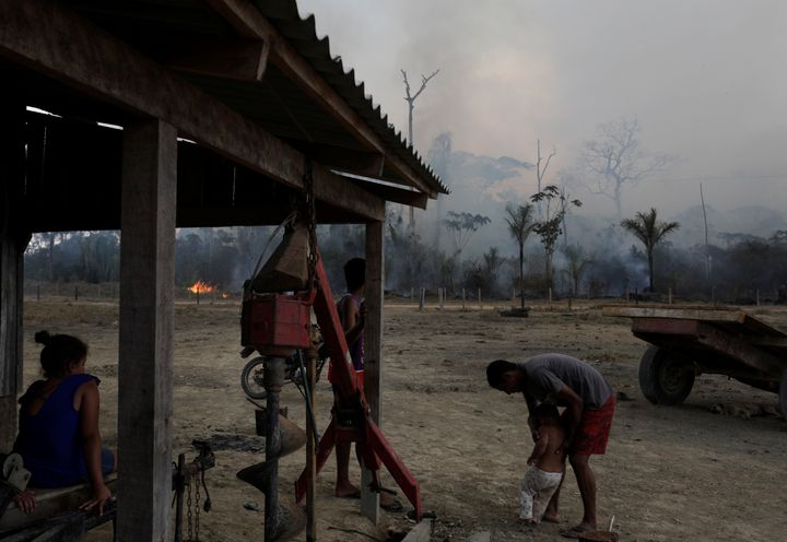 Residents are pictured while a fire burns a tract of Amazon jungle as it is cleared by loggers and farmers near Porto Velho,