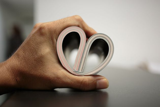 A book curved into a heart shape on man