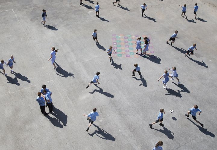 children aged 10-11 running on playground elevated view.