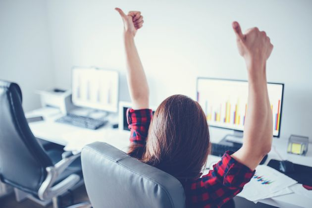 Portrait of happy young successful businesswoman celebrate something with arms up. Happy woman sit at...