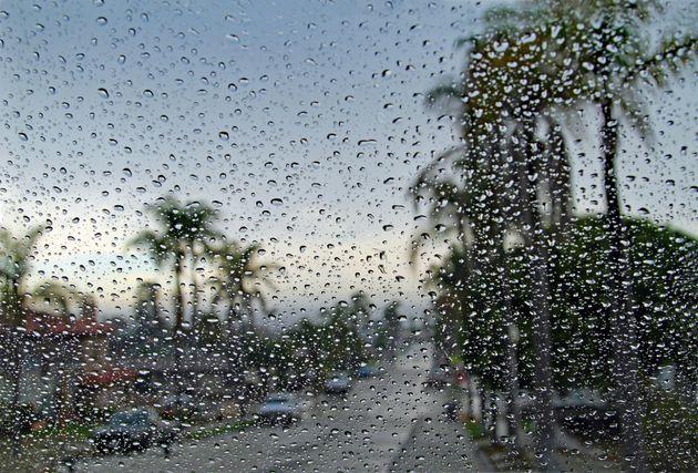Looking towards the ocean through car windshield on a rainy