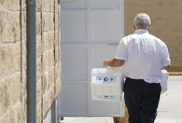 Un operario del Ayuntamiento de Sevilla llega con unas neveras para recoger muestras en la sede de la...