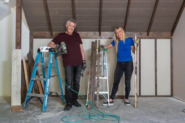 Barry Williams (Greg) and host Jasmine Roth pose after installing old wood planks, salvaged from the...