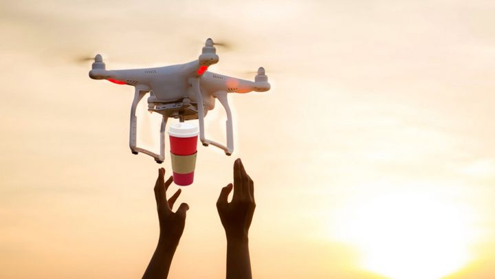 A photoshopped image of a drone delivering Tim Hortons to someone with outstretched hands.