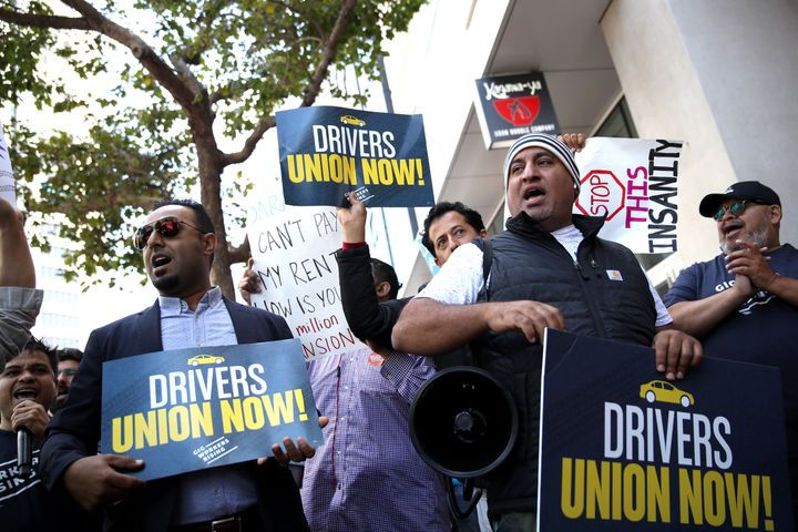 Drivers hold signs during a protest outside Uber headquarters in support of California Assembly Bill 5, Aug. 27, 2019, in San Francisco.