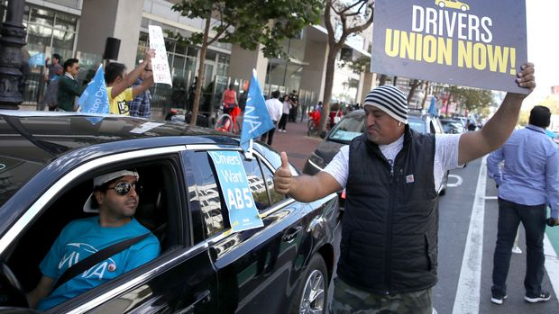 SAN FRANCISCO, CALIFORNIA - AUGUST 27: Rideshare drivers hold signs during a protest outside of Uber headquarters on August 27, 2019 in San Francisco, California. Dozens of Uber and Lyft drivers staged a protest outside of Uber headquarters in support of California assembly bill 5 and to organize a union for rideshare drivers. (Photo by Justin Sullivan/Getty Images)